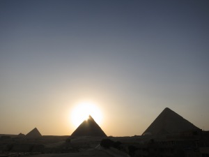 The sun setting behind the Pyramid of Khafre, with the Great Pyramid of Giza on the right and the Pyramid of Menkaure on the left