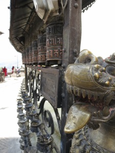 Prayer wheels (left) flanked by bronze lion-headed dragons (right) at Harati Devi Temple