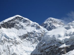 Whispy snow drifts being blown off the summit of Everest (right)
