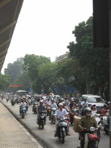 Traffic in Hanoi.  There are a few scooters.