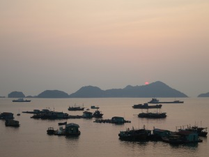 The sun begins to set behind the limestone karst islands of Lan Ha Bay, and behind the fishing fleet of the main port of Cat Ba Island