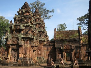 The ornate red stonework of Banteay Srei, complete with moss and grasses growing on the roof on the right