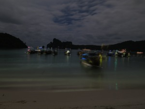 Longtails floating on the water at night in Loh Da Lum Bay