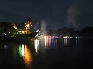 Loh Da Lum Bay (on Ko Phi Phi Don) at night, with the neon lights of its party bars lighting up the beach and bay.  The smoke is from a very large firework which had just been set off.
