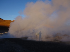 Casting a shadow on the steam from a geyser in the desert at sunrise in southern Bolivia
